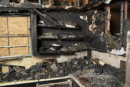 blackened fire damaged cabinets and countertops covered in ash and coal after a fire