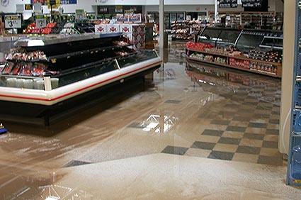 the deli of a grocery store with an inch of mud and water covering the floor